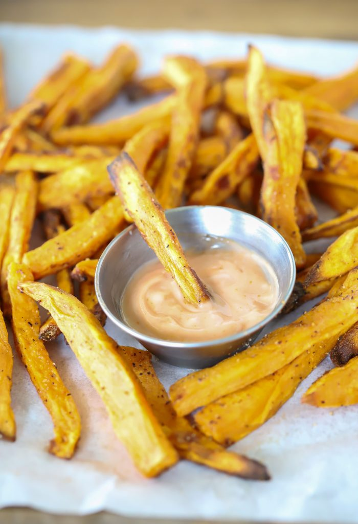 A pile of fries with fry sauce in the middle.